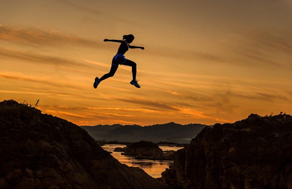 image of woman jumping between rocks